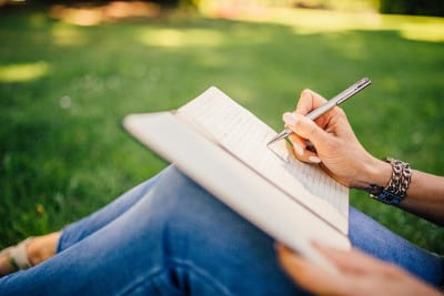 Professional Note Taking - Woman on grass writing in notebook